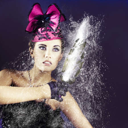 Action and excitment spray the air with a woman in fancy formal fashion holding onto a exploding bottle of champaign as water droplets splash amogst shattering debris in a image titled smashing party photo