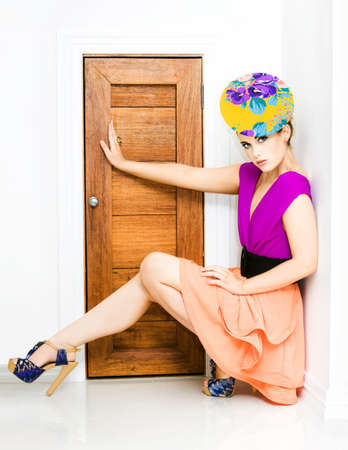 Young trendy woman in colourful fashion outfit squatting down against a wall with her arm and leg extended out blocking a small doorway in a fashion police concept photo