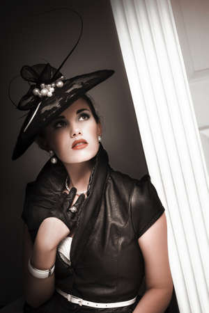 elegant woman wearing black hat with pearls, black leather blouse and black half gloves leaning on a door post photo