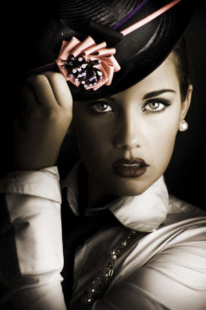 Close-up portrait on the face of a beautiful and mysterious female standing in the shadows halfway between dark and light wearing a stylish flower hat in a image titled face of dark fashion photo