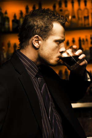 Rough And Tough Serious Male Drinker Downing A Glass Of Alcoholic Beverage Standing In Front Of A Bar In A Depiction Of Hard Stuff photo
