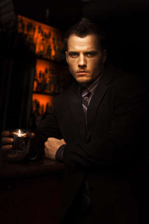 Handsome Tough Young Man With A Serious Look Standing In A Dark Bar With A Drink In A Bar Room Brawl And Fight Club Conceptual Stock Photo - 12977479