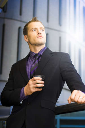 Smart Handsome Businessman Holding Drink In Hand While Staring Off Into The Future Of Dreams And Aspirations photo