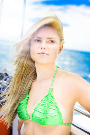 Rays Of Summer Sun. Beautiful young blonde woman in green bikini standing near the ocen lit by the bright rays of the summer sun. Stock Photo - 12977794