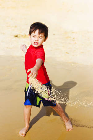 Happy young Asian boy on vacation playing in his shorts on the beach throwing wet sand in a motion action capture photo