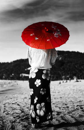 Black and white image of an Asian person walking away across a sandy beach wearing a floral sarong and carrying a parasol in red selective colouring photo
