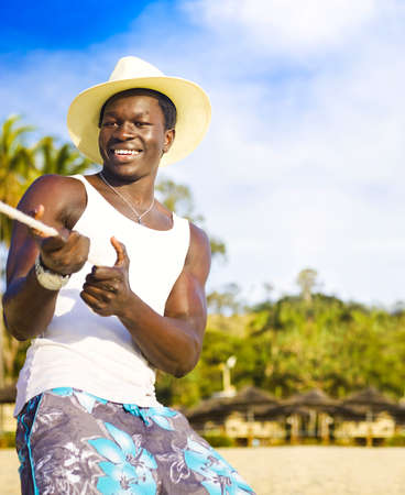Tug Of War. Handsome smiling black man wearing a straw hat exuding health and fitness pulling back on a rope in a tug of war on a beach. photo