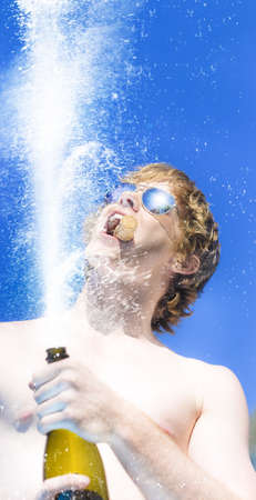 Low angle image of a mans hands holding a champagne bottle with a spray of bubbly and his face above against a blue sky photo
