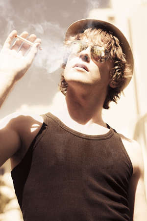 Low angle artistically toned image of a trendy young person in hat and sunglasses puffing on a smoke outdoors photo