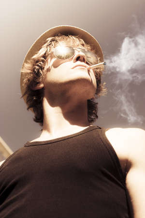 Low angle view of a handsome blonde macho male model in sunglasses and hat with a lit cigarette in the corner of his mouth photo