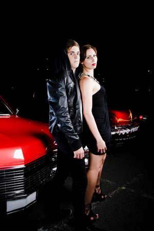Fifties couple in retro black clothing leaning nonchalantly against the hood of their red vintage car glancing at the camera while watching a movie at a night drive-in Stock Photo - 12978371