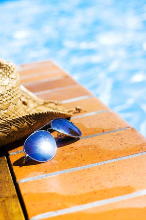 Pair of sunglasses with lens sun flare and straw hat abandoned by a bather on wet tiles alongside a sparkling swimming pool in a summer vacation concept Stock Photo - 12978492
