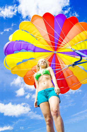 Low angle view of a young woman in a bikini standing beneath a colourful inflated parasail canopy with a harness against cloudy blue sky in summer Stock Photo - 12978529
