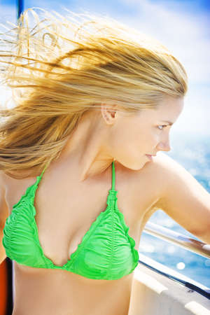 Beautiful young blonde female tourist with her hair blowing in the ocean breeze looking out over the sea on a travel cruise Stock Photo - 12978532