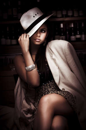 Stylish Trendy And Fashionable Female Model Wearing Slanting Hat And Coat Over A Elegant Evening Dress Inside A Dark Bar In A Depiction Of Dark Fashion photo