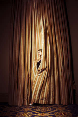 Theatre Performer peeking out through heavy gold curtains as she awaits her cue to make an entrance on stage photo