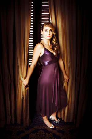 Beautiful actress wearing a purple evening dress with long curly blonde hair posing in front of ornate gold curtains for her portrait at the premiere of her latest film  Stock Photo - 13036971