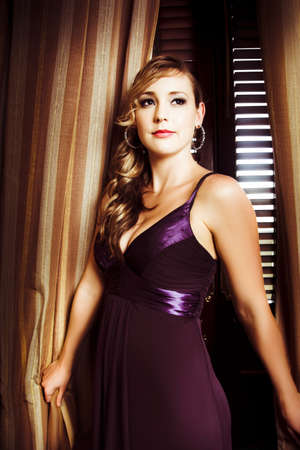 Beautiful glamour model with curled hair standing indoors in front of a curtain in elegant dark purple evening dress with a plunging neckline photo