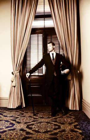 Retro male servant standing guard at a curtained entranceway holding his masters cane and tophat while he waits patiently to be of service  photo
