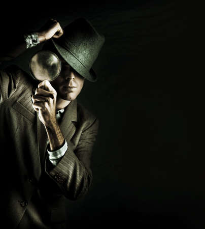 Creative Grunge Portrait Of A Man Holding A Magnifying Glass While On A Search And Find Mission To Solve A Crime Scene Investigation, Isolated On Black photo