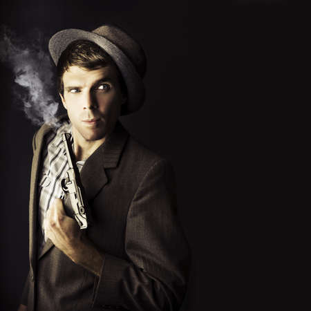 Dark Studio Image Of A Professional Hit Man Wearing Vintage Suit Holding A Retro Hand Gun In A Dangerous Business Conceptual, Isolated On Black Background photo