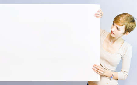 Pretty businesswoman holding a blank sign with room for your text photo