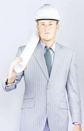 Engineer wearing a nice striped suit while carrying rolled up engineering plans on his shoulder in a urban development and town planning conceptual photo