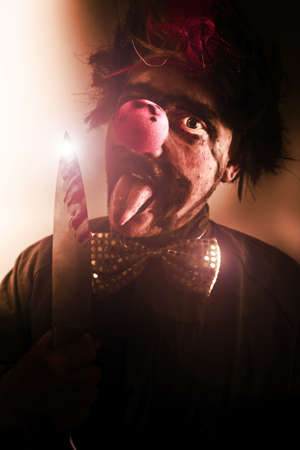 Sinister Portrait Of A Frightening Evil Clown With Creepy Expression Holding A Bloody Knife Or Cleaver Stock Photo - 13177749