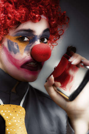 Portrait Of A Female Clown With Red Hair And Big Red Nose Holding A Hip Flask In One Hand Stock Photo - 13178196