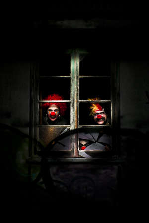 Three Evil Looking Clowns Peering Out The Window Of A Shadowy Building photo