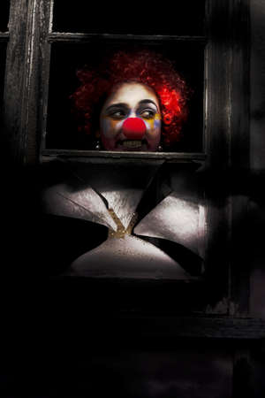 Head Of A Clown Showing Through Dark Shadows Of An Old Window Stock Photo - 13177716