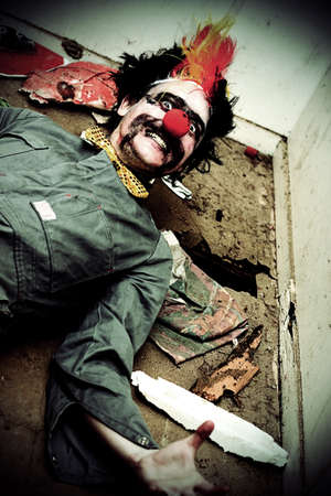 Mr Sleepy The Creepy Clown Lays On A Holey Rubbish Littered Floor With A Horrific Smile Across His Frightening Face photo