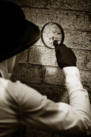 Retro Private Eye Detective Searching For Clues By Investigating A Suspected Crime Scene Wall With A Magnifying - Looking Glass Stock Photo - 13177990