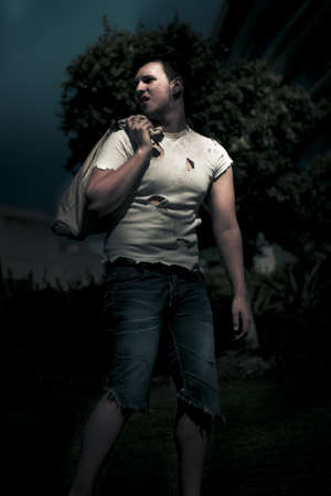 Holes In His Shirt And Carrying A Sack Of Personal Belonging The Night Wanderer Walks The Urban Streets In The Darkness Of Late Nighttime Stock Photo - 13177598
