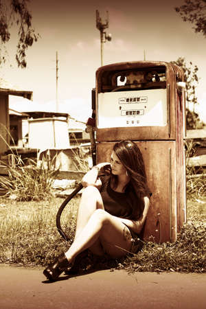 A Woman Sits By A Petrol Pump In The Ghost Town Named Oil And Gas Waiting For A Environmentally Friendly Viable Alternative In A Energy And Environment Concept photo
