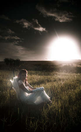 Peace Harmony And Tranquility Is The Scene As A Lady Angel Sits In The Countryside With A Sunset Landscape Background In A Dreamy Image Titled Field Of Dreams Stock Photo - 13178739