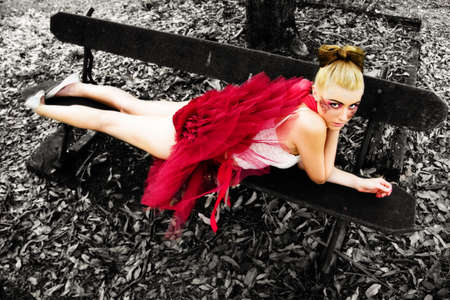 Autumn Or Fall Concept With A Woman In A Red Tutu Relaxing On A Wooden Seat With Leaves Below, Image With Black And White Background photo