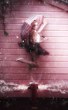 Creative Abstract Art Of A Fashion Dance With A Water Dancer Ballerina Woman With Umbrella Dancing In The Pouring Rain On A Burst Fire Hydrant Flooding Water photo