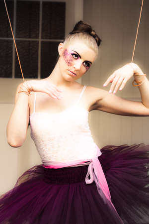 Marionette Doll Wearing Tutu Or Leotard Hanging Or Suspended On Strings And Cords In A Artistic Representation Of Management Dominance Control And Power photo
