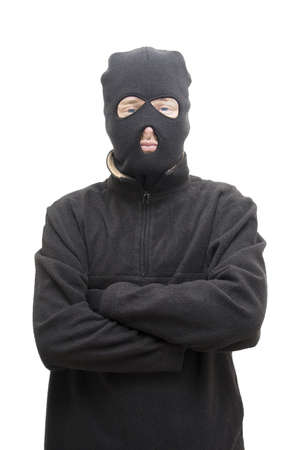 A Smug Looking Masked Assailant Stands With His Arms Crossed Front On In A Studio Portrait photo