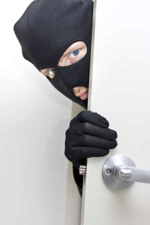 A Masked Intruder Peers Around The Corner While Breaking In A Properties Front Door  photo