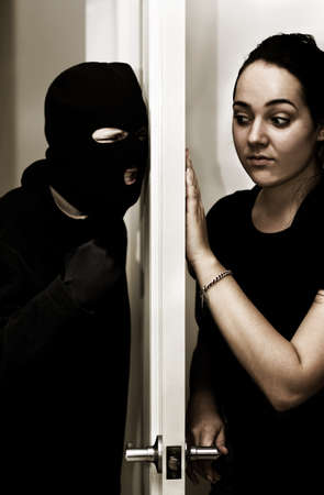 A Violent Intruder Bashes On A Door While A Female Occupant Hesitantly Opens Up Stock Photo - 13200974