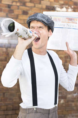 Paperboy Shouts Out The Latest Through His Rolled Up Newspaper In An Act Of Selling News photo