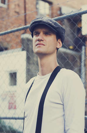 Man Of The Great Depression Stands In A Half Body Portrait Wearing A Retro Style Flat Cap And Suspenders With An Urban Fence And Building In Background photo