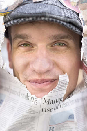 Journalist Pushes His Face Through A Ripped Hole In A Newspaper To Symbolise Being The Face Of The News photo