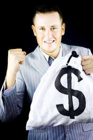 Successful young man in stylish grey suit raising his fist in jubilation at his latest windfall and wealth as shown by the large money bag full of dollars that he is gleefully clutching in his hand photo
