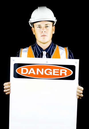 Man with construction helmet holding blank danger sign on black background photo