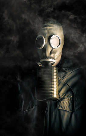 Eerie atmospheric portrait of a soldier in a gas mask and canister with noxious fumes swirling about his head in the darkness in a biohazard, death and destruction concept Stock Photo - 13235432