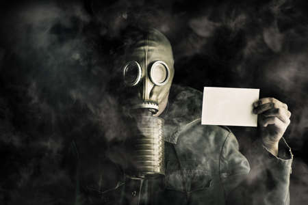 Environmental pollution concept with a man wearing a gas mask in a smoky polluted atmosphere holding up a blank ID card to identify himself under his protective gear worn to survive photo