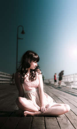 Attractive Young Woman In Dress Resting And Relaxing On Wooden Walking Bridge In A Dreamy Sea Side Summer Holiday Vacation photo